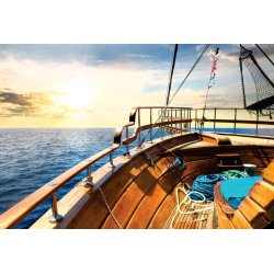 Wall mural wooden sailboat in the sea at sunrise